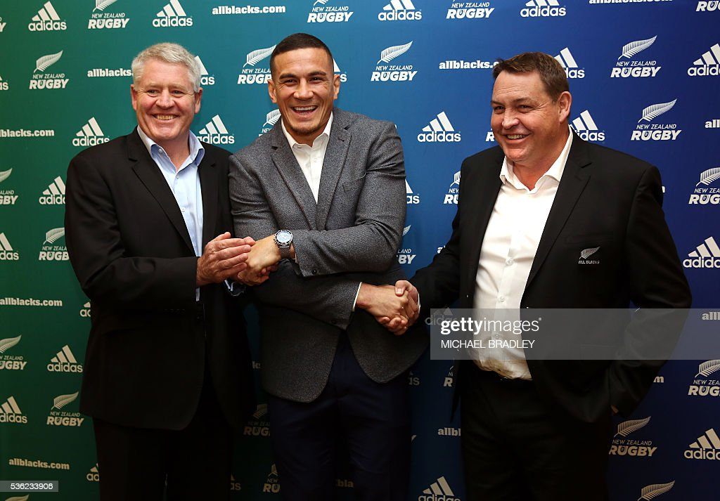 All Black Sonny Bill Williams (C) with NZRU Chief Executive Steve Tew (L) and All Blacks Coach Steve Hansen (R) shake hands after it was announced that Sonny Bill Williams has signed a three year deal with the New Zealand Rugby Union and will play for the Auckland Blues next year in Auckland on June 01, 2016. / AFP / MICHAEL