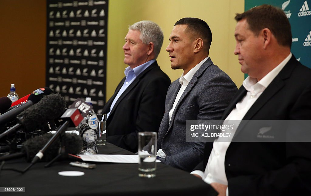 All Black Sonny Bill Williams (C) with NZRU Chief Executive Steve Tew (L) and All Blacks Coach Steve Hansen speak to the media after it was announced that Sonny Bill Williams has signed a three year deal with the New Zealand Rugby Union and will play for the Auckland Blues next year in Auckland on June 01, 2016. / AFP / MICHAEL