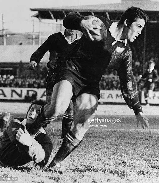 All Blacks centre Bryan George Williams manages to break the tackle of British Lions captain John Dawes during the first test match between the Lions...