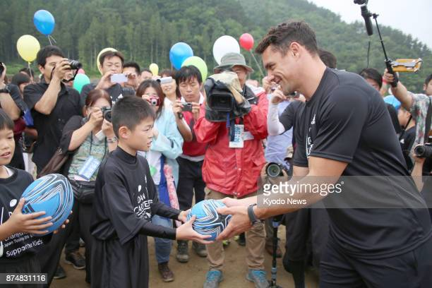 All Blacks legend Dan Carter hands autographed balls to children on July 17 during a promotional event at the construction site of the 2019 Rugby...