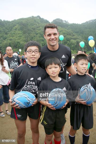 All Blacks legend Dan Carter poses for a photo with children on July 17 during a promotional event at the construction site of the 2019 Rugby World...