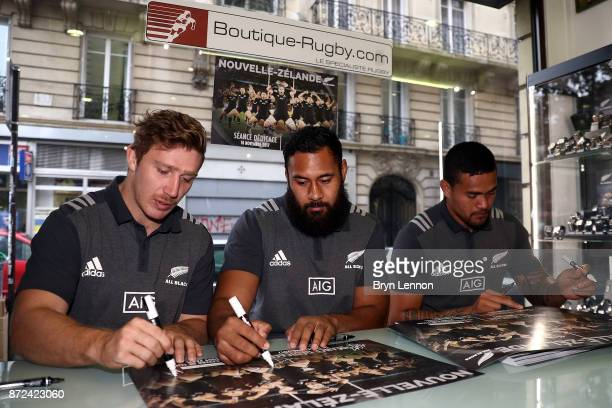 All Blacks Nathan Harris and Patrick Tuipulotu sign posters during an autograph session at Boutique Rugby on November 10 2017 in Paris France