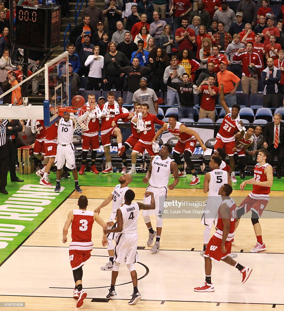 All eyes are on the ball as it drops in for a gamewinning threepointer by Wisconsin guard Bronson Koenig obscured behind backboard as time expires...