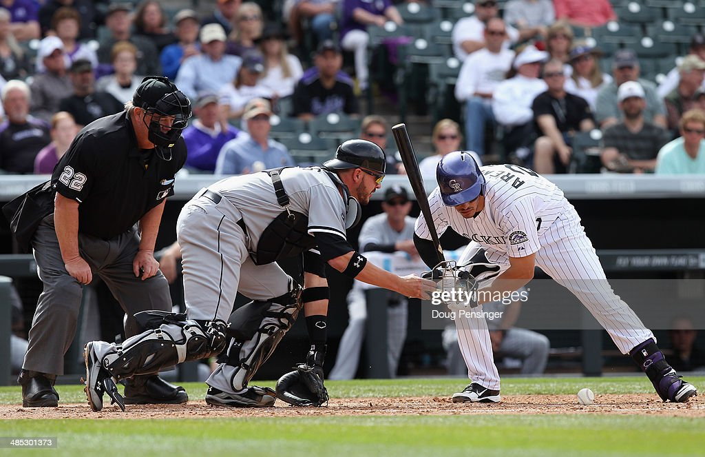 All eyes are on the ball as Nolan Arenado of the Colorado Rockies takes an at bat and catcher Tyler Flowers of the Chicago White Sox collects the...