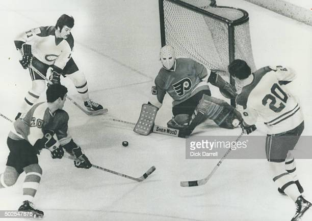 All eyes are rivetted on the puck Montreal Canadians' Yvon Lambert and Peter Mahovlich along with Philadelphia Flyers' defenceman Jim Watson and...