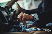 Cropped shot of a businessman changing the gears of a car