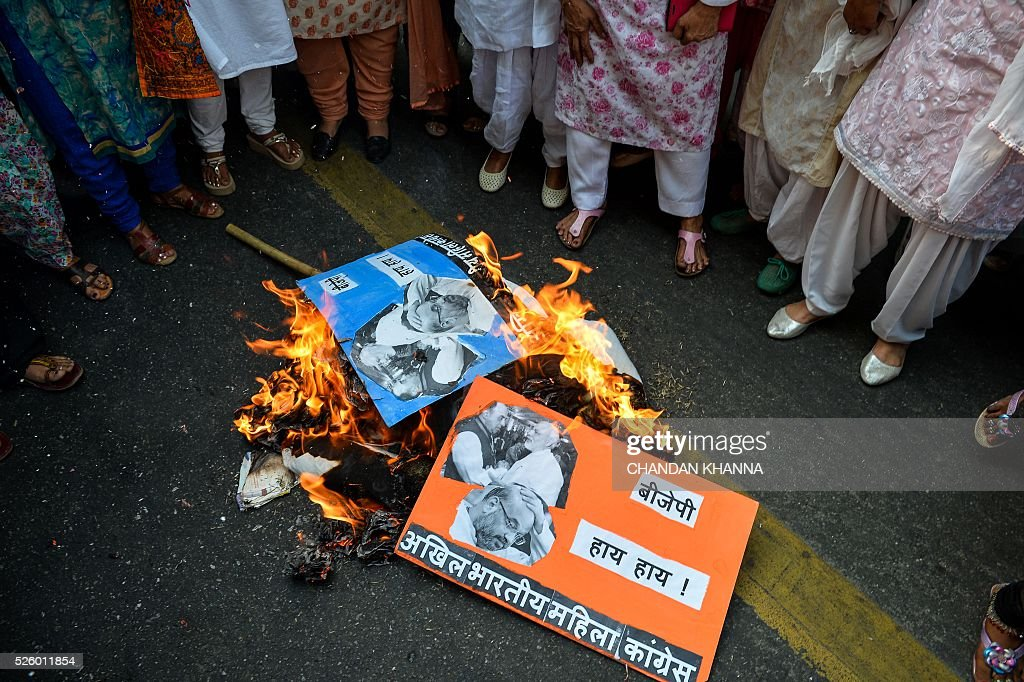 All India Mahila Congress supporters burn effigies of Indian Prime Minister Narendra Modi and ruly Bhartiya Janta Party (BJP) President Amit Shah as they protest against the BJP government, accusing them of defaming the All India Congress Party in parliament in New Delhi on April 29, 2016. India's government said April 28 it has asked Britain to extradite British consultant Christian Michel James over a scandal-hit deal the previous government agreed with Anglo-Italian firm AgustaWestland to supply helicopters to Delhi. The deal has set off a fresh political storm in New Delhi after an Italian court reportedly cited James as alleging India's opposition leader Sonia Gandhi and others took more than $27 million in bribes to swing the deal for AgustaWestland. / AFP / CHANDAN