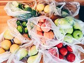 Apples, peachs, tomatoes, pears, cucumbers, avocado packed in plastic bags after shopping at local eco market in Marmaris, Turkey