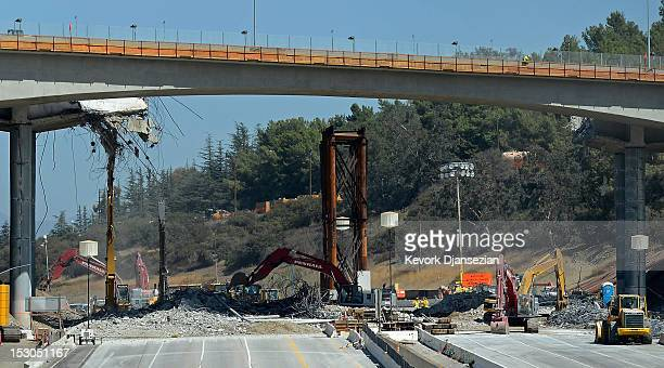 All lanes of the 405 Freeway are empty except for construction trucks as crews continue to demolish a portion of the Mulholland Drive bridge along...