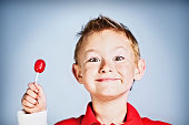 All mine! Little boy holding red lollipop smiles in delight