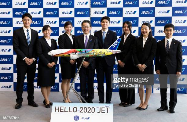 All Nippon Airways Co President and Chief Executive Office Yuji Hirako center left and newly hired employees pose with a model of ANA's aircraft with...