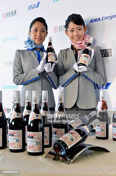 All Nippon Airways staffs pose with bottles of Beaujolais nouveau at Tokyo International Airport on November 4 2014 in Tokyo Japan The wine is...
