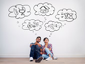 Shot of a young couple with thought bubbles illustrated above them on a white wall