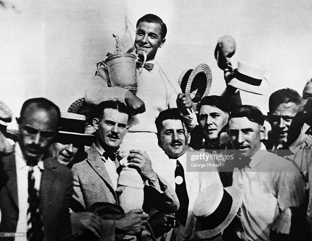 All smiles, and with his trophy in arms, Gene Sarazen, the twenty one year old golfer of Pittsburgh, PA., an ex-caddie from the Apawmis Club of Rye, NY, is shown here being carried on the shoulders of enthusiastic fans after winning the golf crown--the leading trophy in the game--with a score of 288 on the links of the Skokie Country Club; Glencoe, IL.