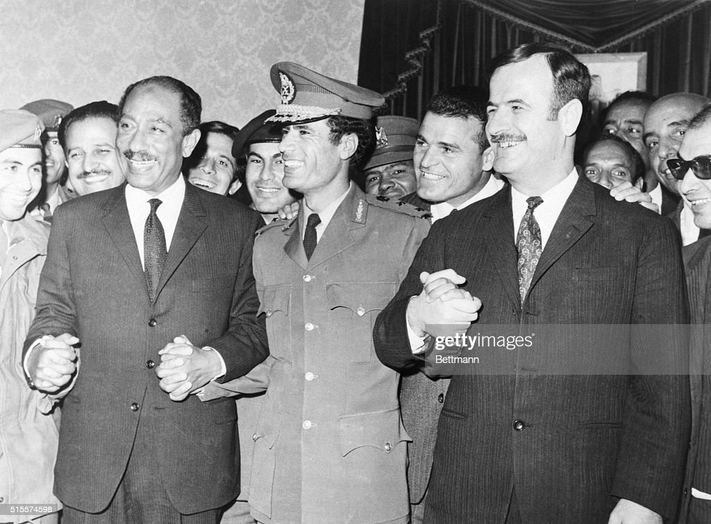 All smiles, Pres. Anwar Sadat of Egypt, Premier Col. Moammar Khadafy of Libya, and Pres. Lt. Gen. Hafez Assad of Syria, join hands after signing agreement establishing the 'Federation of Arab Republics' here April 17th, embracing nearly half the population of the Arab world. Details of the federation will be announced late April 17th.