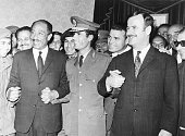 All smiles Pres Anwar Sadat of Egypt Premier Col Moammar Khadafy of Libya and Pres Lt Gen Hafez Assad of Syria join hands after signing agreement...