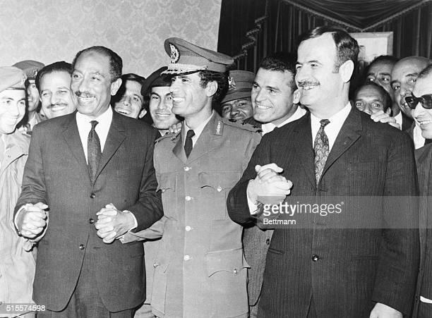 All smiles Pres Anwar Sadat of Egypt Premier Col Moammar Khadafy of Libya and Pres Lt Gen Hafez Assad of Syria join hands after signing agreement...