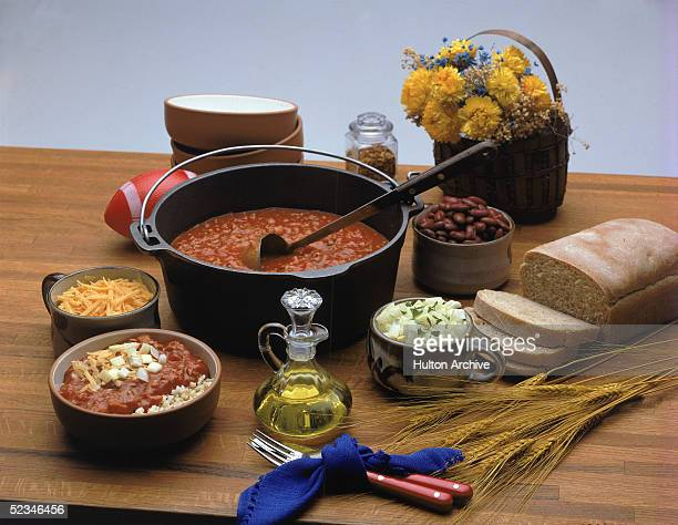 All the items necessary for a Mexicanthemed chili feast sit on a wooden surface including a cauldron of chili a loaf of bread a bowl of brown rice...