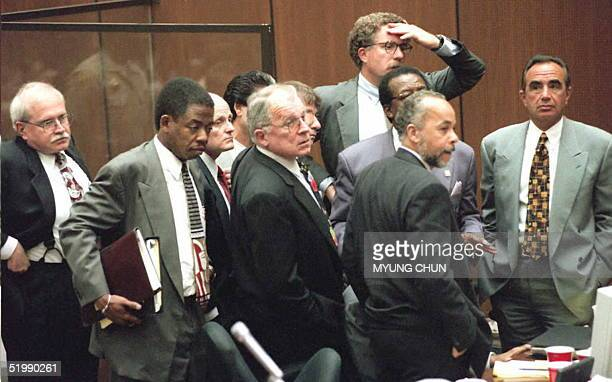 All the members of the OJ Simpson defense team huddle around Simpson at the end of a controversial court day 29 August in Los Angeles Tapes of racist...