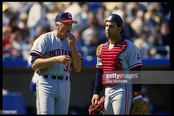 All time great Atlanta Braves pitcher Phil Niekro now a coach of the Cleveland Indians talks with catcher Chris Bando of the Indians Mandatory Credit...