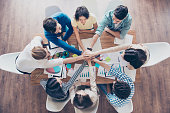 All together! Conception of successful teambuilding. Topview of businesspeople putting their hands on top of each other in nice light workstation, wearing casual clothes