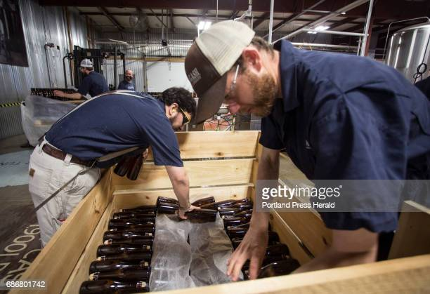 Allagash employees Salim Raal left and Brendan McKay stack bottles of Golden Brett a limited release beer feremented with a house strain of...