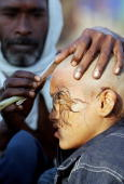 A young Indian Hindu devotee gets his head shaved on the banks of Sangam the confluence of the Ganges Yamuna and mythical Saraswati rivers in...