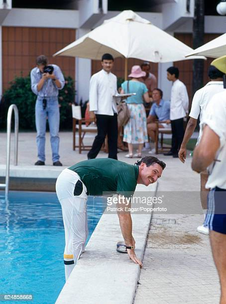 Allan Border of Australia climbs out of a hotel swimming pool after been thrown in by his teammates in celebration of Australia winning the Reliance...
