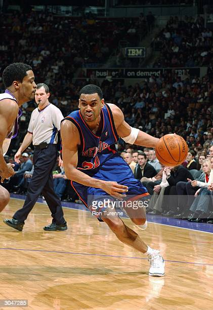 Allan Houston of the New York Knicks drives past Morris Peterson of the Toronto Raptors on March 5 2004 at the Air Canada Centre in Toronto Canada...