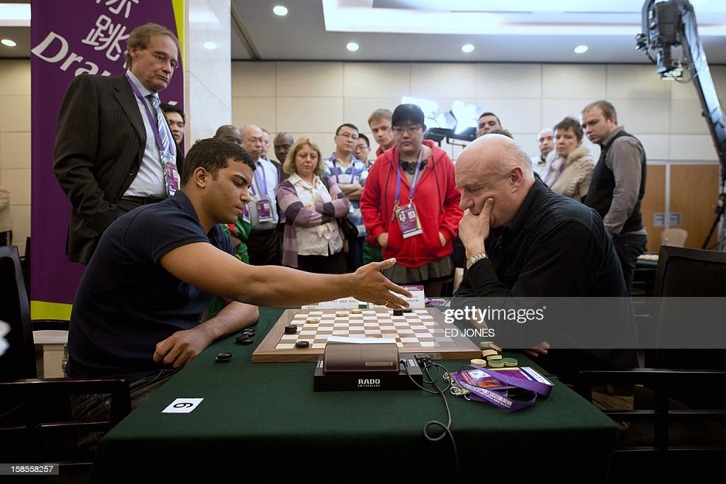Allan Igor Moreno Silva (L) of Brazil competes against Anatoli Gantwarg (R) of Belarus during a draughts competition at the Beijing 2012 World Mind Games Tournament in Beijing on December 19, 2012. Some of the world's top chess players went eye-to-eye in the year's highest-level 'blindfold' chess tournament -- seen by some as the toughest challenge in the game. Unable to physically see their own or their opponent's past moves, the players summoned headache-inducing levels of concentration to fight for gold in a silent conference room, lined up in front of laptop screens showing a blank board. AFP PHOTO / Ed Jones