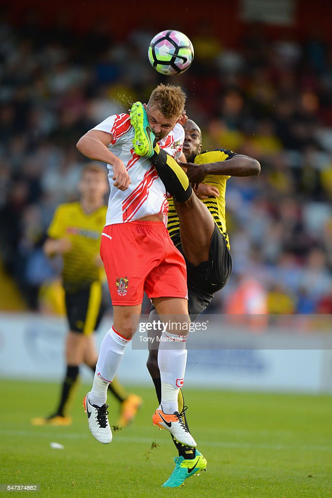 Allan Nyom of Watford tackles Matt Godden of Stevenage during the PreSeason Friendly match between Stevenage and Watford at The Lamex Stadium on July...