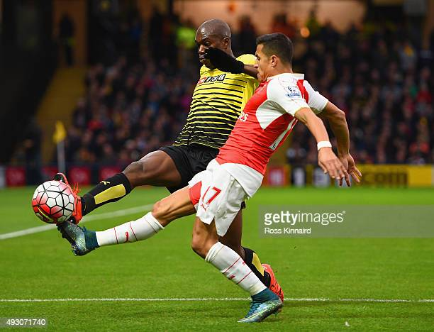 AllanRomeo Nyom of Watford and Alexis Sanchez of Arsenal compete for the ball during the Barclays Premier League match between Watford and Arsenal at...