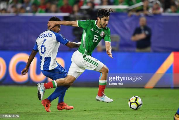 Allans Vargas of Mexico brings the ball up field past Bryan Acosta of Honduras in a quarterfinal match during the CONCACAF Gold Cup at University of...
