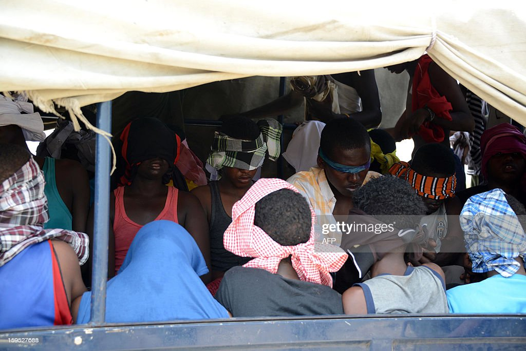 Alleged Al-Shabab rebel fighters are loaded blindfolded onto a police truck on January 15, 2013 after being arrested during an operation against the fundamentalist group in Mogadishu. Somalia's Al-Qaeda-linked Shebab said on January 14 a French soldier wounded and captured during a failed hostage rescue raid has died and published pictures of the purported commando chief's body. France's military operation on January 12 to free a French spy held hostage by the Shebab since July 2009 was a failure, with another French soldier killed and the situation of the hostage unclear. AFP PHOTO/Mohamed ABDIWAHAB
