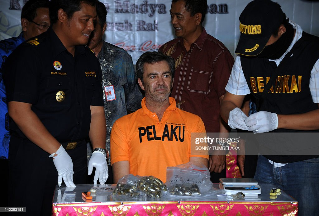 Alleged drug mule Australian Edward Norman Myatt (R), aged 54, sits in front of 72 capsules (weight 1.1 kilograms) of hashish and one capsule (7 grams) of methamphetamine during press conference at the Custom office in Denpasar on March 2, 2012. Myatt allegedly swallowed 72 capsules of hasish and methamphetamine, and attempted to smuggle them into the Indonesian resort island of Bali from Bangkok, official said. If convicted of smuggling the drugs into Indonesia, the Australian could face the death penalty.