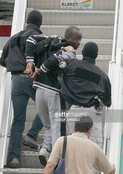 Alleged French gang leader Youssouf Fofana is escorted handcuffed by two plainclothes policemen on the gangway of a Parisbound plane at Abidjan...