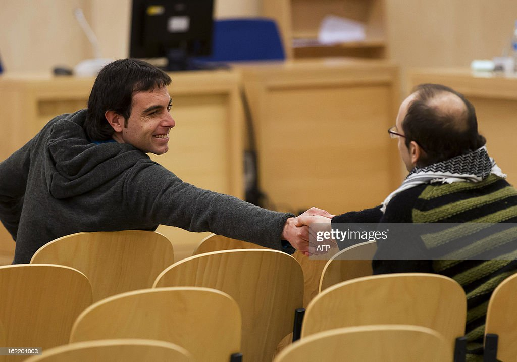 Alleged members of the Basque armed separatist group ETA Asier Badiola and Ibon Iparraguirre shake hands in the courtroom as they attend their trial at the National Court in Madrid on February 18, 2013. Asier Badiola and Ibon Iparraguirre are charged with allegedly taking part in 2008 in a car bomb attack against an Ertzaintza station, Basque police station, in Ondarroa, injuring three police officers and five civilians. AFP PHOTO / POOL / CHEMA MOYA