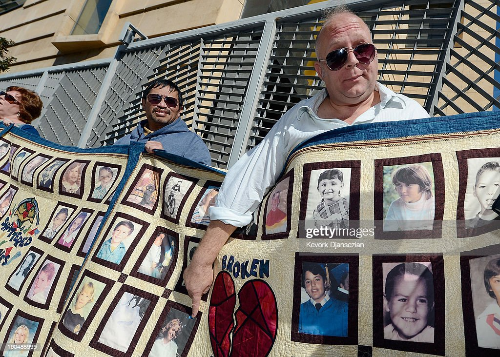 Alleged sexual abuse victim Jorgen Olson (R) points to his photo on quilt with pictures of other alleged victims of sexual abuse by priests in the Catholic Archdiocese of Los Angeles during a news conference urging victims to come forward on February 1, 2013 at Cathedral of Our Lady of the Angels in Los Angeles, California. Retired Cardinal Roger Mahony of Catholic Archdiocese of Los Angeles, who avoided criminal charges over the way he handled pedophile priests during his career, was reportedly stripped of his archdiocese duties February 1, by his successor Archbishop Jose Gomez.