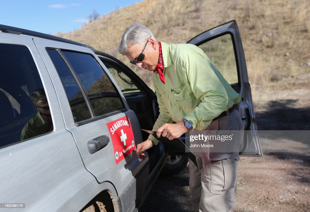 Allen Buchanan, a volunteer for the non-profit Samaritans group, places a sign on a Samaritan vehicle near the Mexican border on March 6, 2013 in Walker Canyon, Arizona. The Samaritans group distributes water along immigrant trails with the aim of reducing immigrant deaths due to dehydration during their long trek from Mexico into the United States, often through remote desert areas.