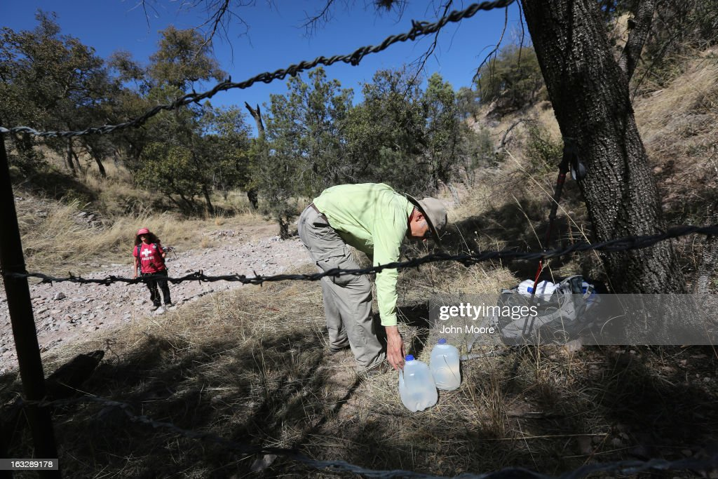 Allen Buchanan, a volunteer for the non-profit Samaritans, places jugs of drinking water along an immigrant trail at the Mexican border fence on March 6, 2013 in Walker Canyon, Arizona. The Samaritans group distributes food and water along the trails with the aim of reducing immigrant deaths due to dehydration during their long trek from Mexico into the United States, often through remote desert areas.
