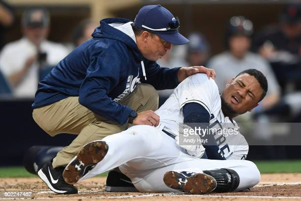 Allen Cordoba of the San Diego Padres is helped by trainer Paul Navarro after being hit by a pitch during the game against the Detroit Tigers at...