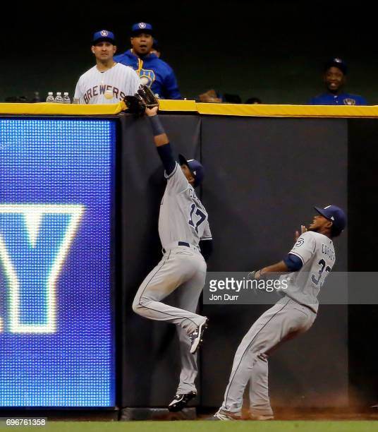 Allen Cordoba of the San Diego Padres is unable to catch the walkoff homerun ball of Eric Thames of the Milwaukee Brewers as Franchy Cordero looks on...