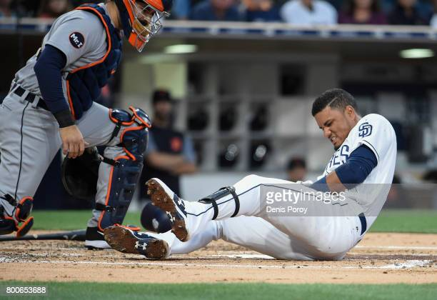 Allen Cordoba of the San Diego Padres lies on the ground next to Alex Avila of the Detroit Tigers after being hit with a pitch during the third...