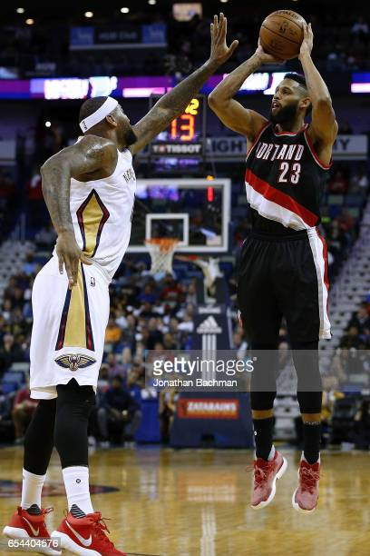 Allen Crabbe of the Portland Trail Blazers shoots over DeMarcus Cousins of the New Orleans Pelicans during the first half of a game at the Smoothie...