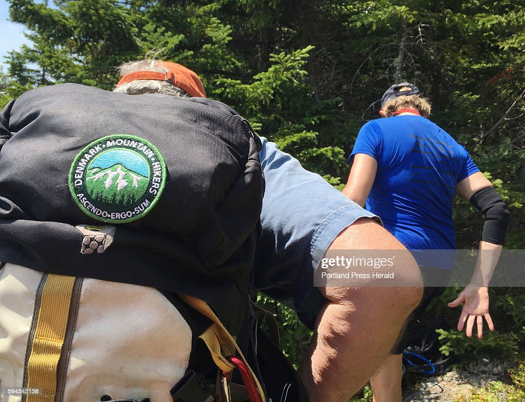 Allen Crabtree shoulders his pack that has a Denmark Mountain Hikers patch sewn on it while preparing to continue the climb up Caribou Mountain in...