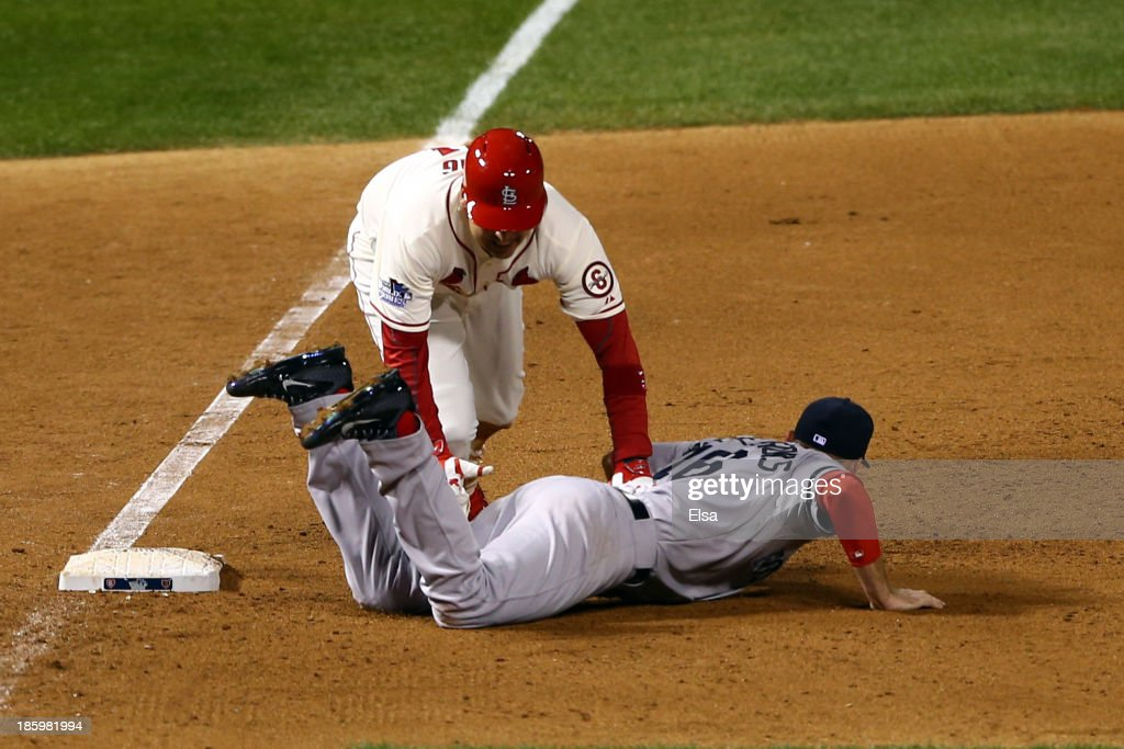 Allen Craig #21 of the St. Louis Cardinals gets tripped up by Will Middlebrooks #16 of the Boston Red Sox during the ninth inning of Game Three of the 2013 World Series at Busch Stadium on October 26, 2013 in St Louis, Missouri.