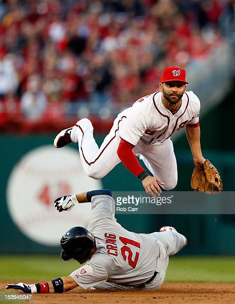 Allen Craig of the St Louis Cardinals slides safely into second base as Danny Espinosa of the Washington Nationals throws the ball to first to force...