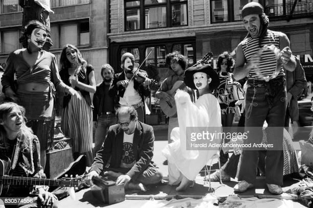 Allen Ginsberg seated on the ground at center with members of the Julian Theater San Francisco California 1971