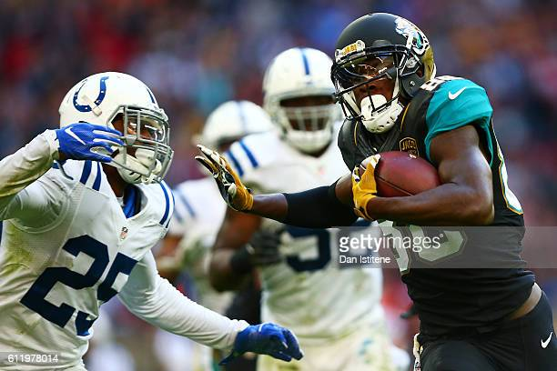 Allen Hurns of the Jacksonville Jaguars hands off Patrick Robinson of the Indianapolis Colts to score a touchdown during the NFL game between...
