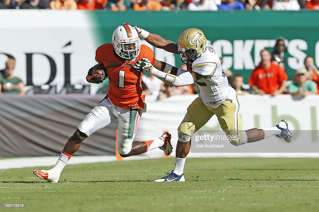 Allen Hurns #1 of the Miami Hurricanes runs with the ball and eludes the tackle of Demond Smith #12 of the Georgia Tech Yellow Jackets on October 5, 2013 at Sun Life Stadium in Miami Gardens, Florida.